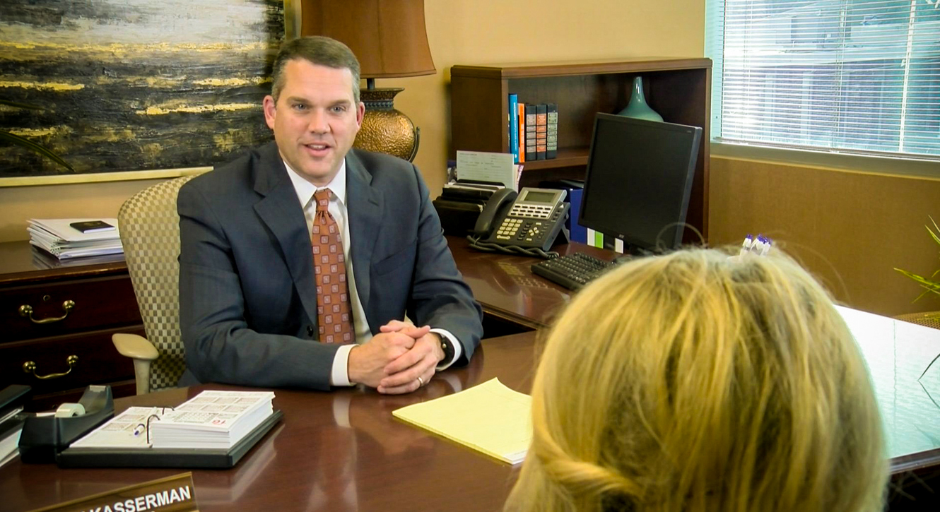 Image of a loan officer seated at his desk speaking with a customer about a loan request.