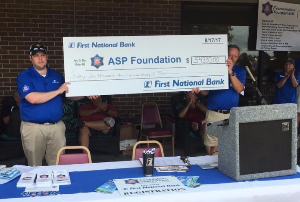 Will Brewer and Frank Guinn display a giant check of the proceeds from the ASP Foundation Golf Tournament.