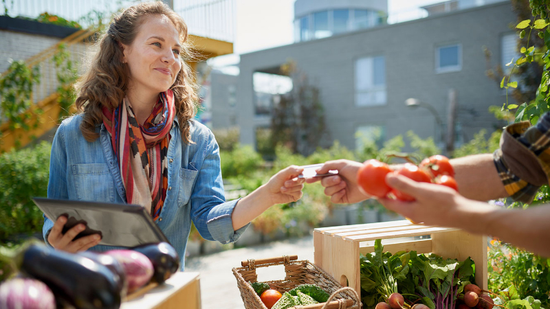 Woman receives a credit or debit card from a customer who is purchasing food at an outdoor market.