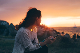 A woman gazing into a sunset over the sea, phone in hand.