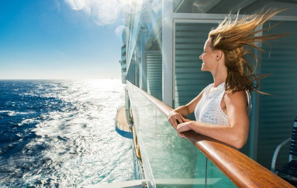 A young lady stands on the deck of a cruse ship and happily looks at the beautiful ocean and sky.